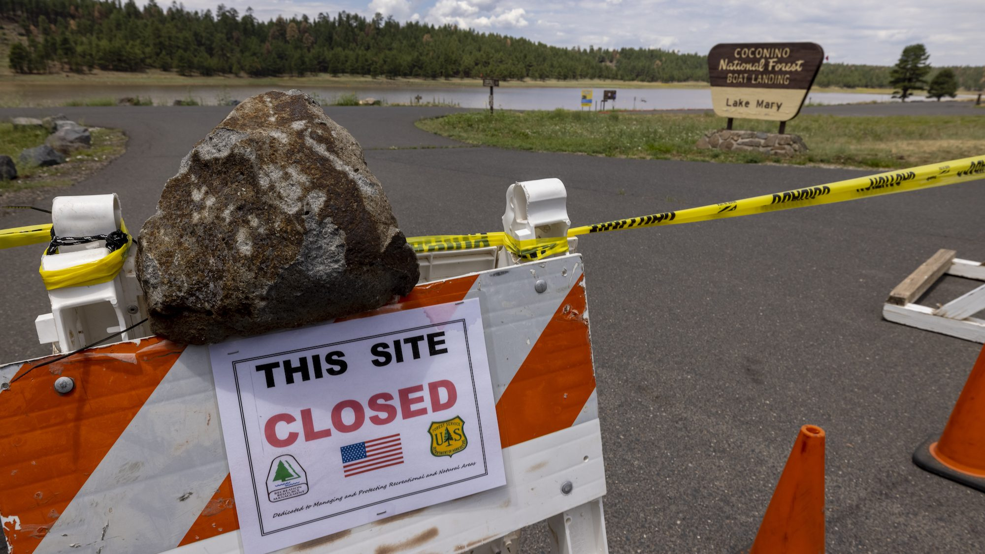 a big rock holds an orange and white sign that says