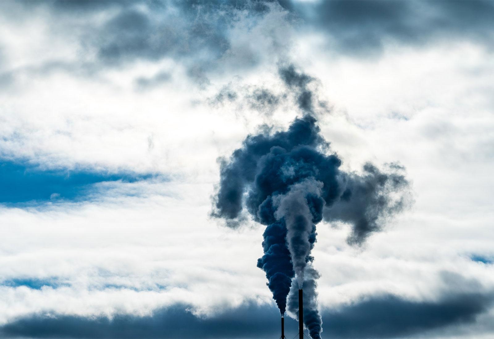 Smokestacks and smoke against a cloudy sky