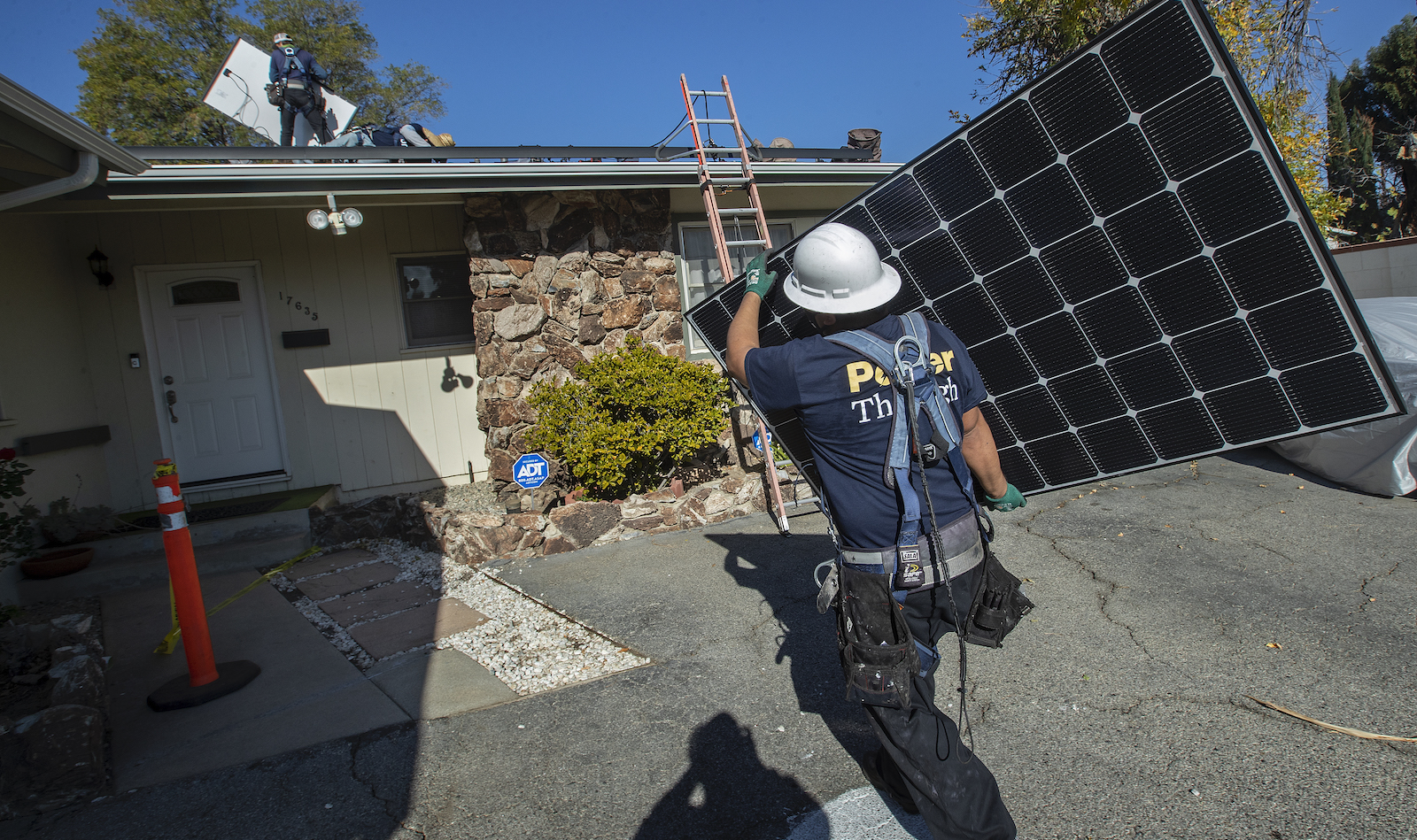 solar panel installer carries a solar panel toward a house