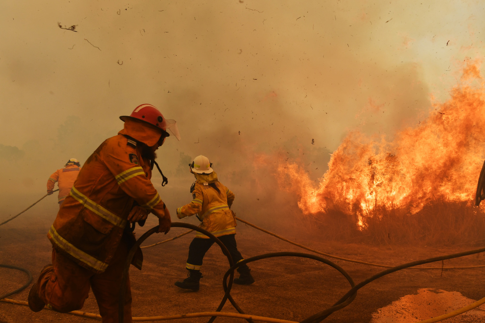 firefighters in full protective gear lift hoses as a fire rages behind them