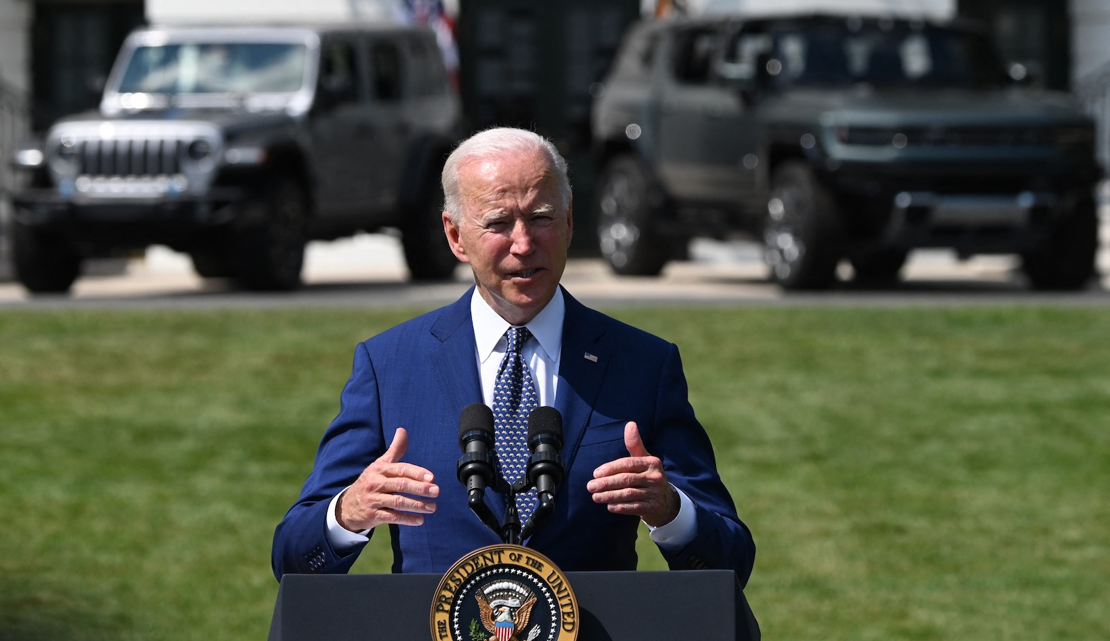 Biden stands in front of two electric vehicles.