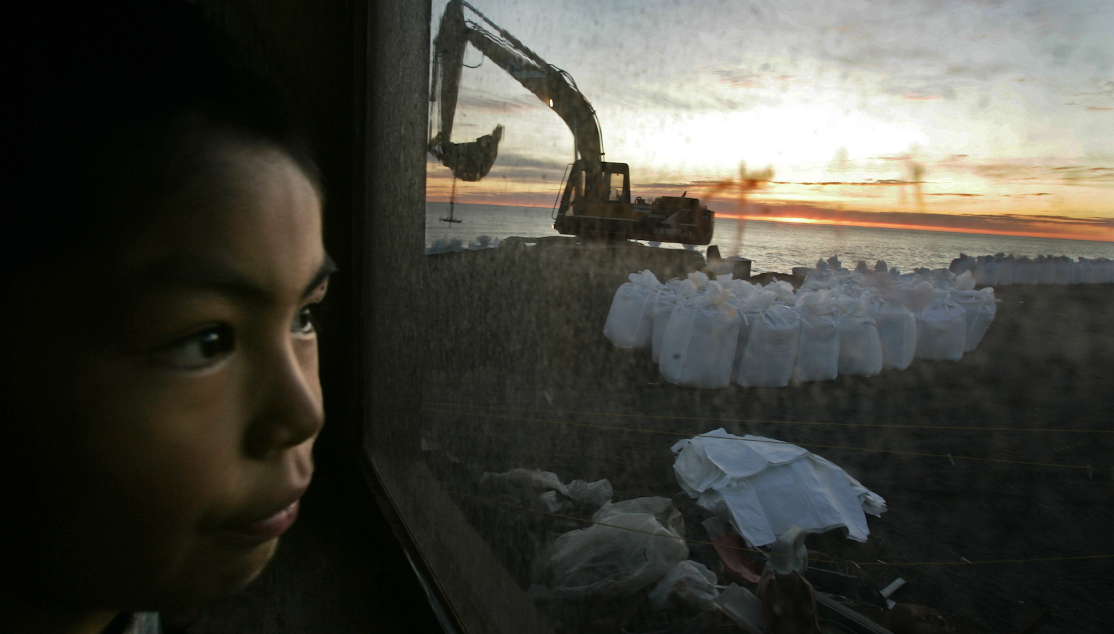 A boy watches workers fill sandbags for a seawall to shield his island from the Chukchi Sea.