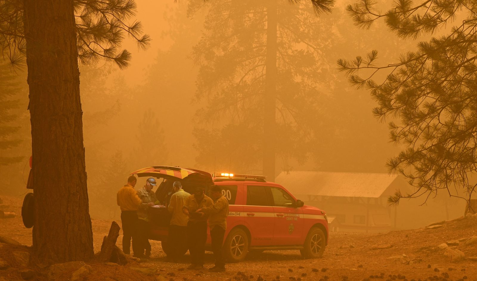 Firefighters fight the Dixie Fire on July 26 amid smoky skies.