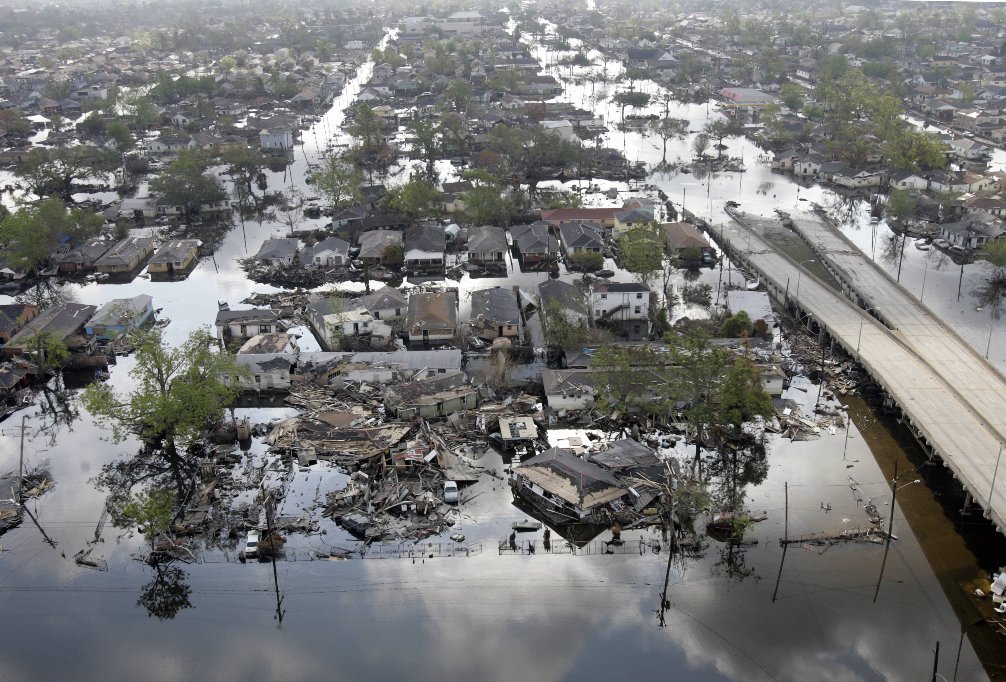 An aerial shot of houses destroyed as well as a highway and roads flooded.