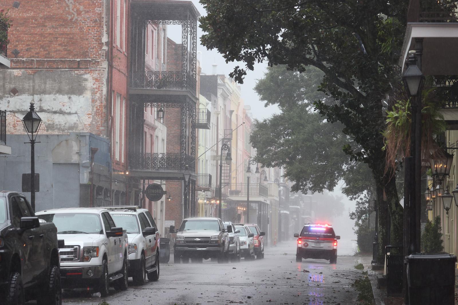 An emergency response vehicle cruises through a street battered by Hurricane Ida