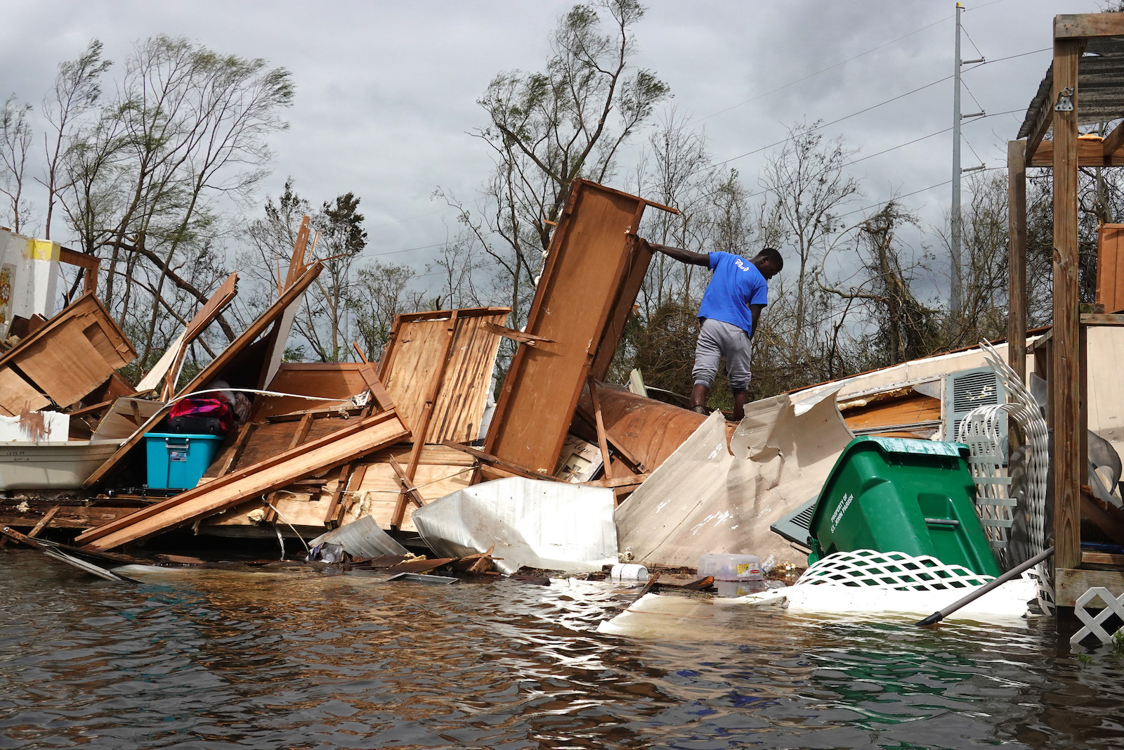 A man stands on top of a pile of furniture and home furnishings destroyed during Hurricane Ida.