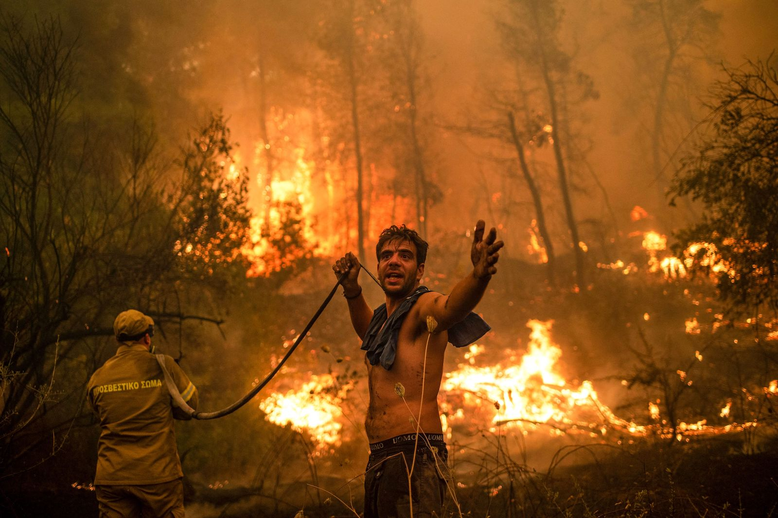 a shirtless man holding a fire hose gestures at the viewer as wildfires blaze behind him