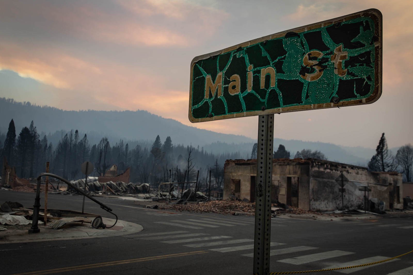 """A charred green """"main street"""" sign with a burned mountainous background"""