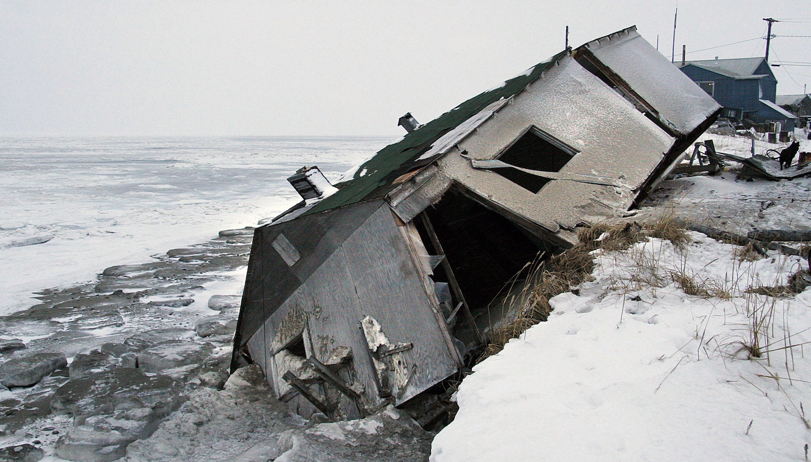 An abandoned house collapses into the water due to coastal erosion in Alaska.