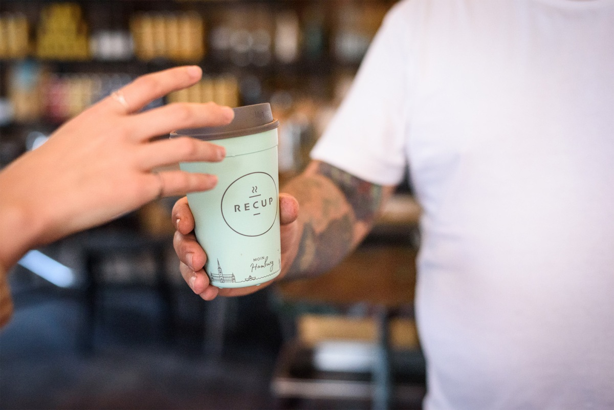 A person reaches for a green coffee cup with brown lid. the cup is labeled ReCUP