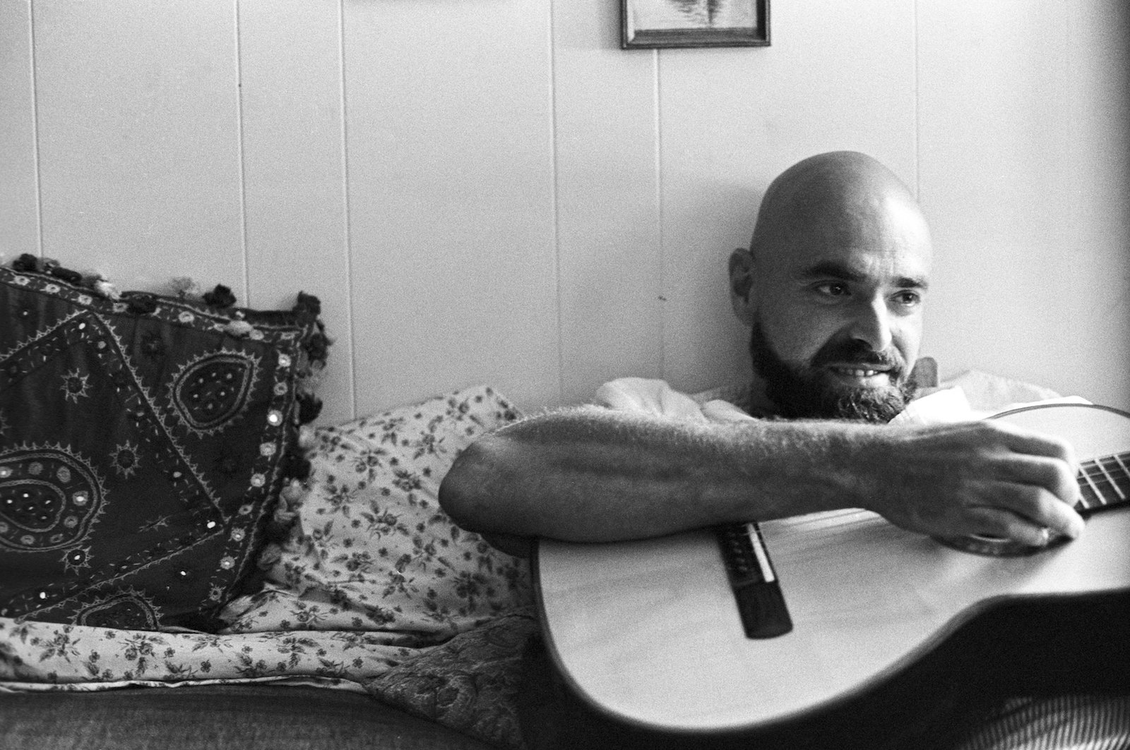 a black and white image of shel silverstein, who is a bald man with a beard holding a guitar