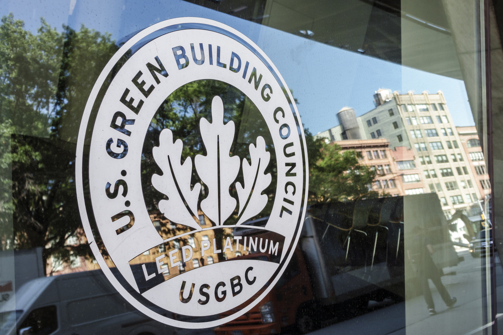 a logo for the US Green building Council on a door -- with three leaves in the center of the design