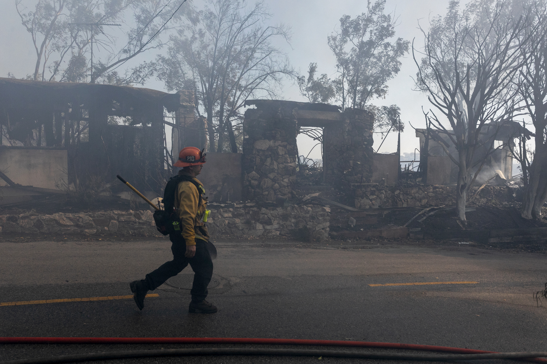 A firefighter wearing a yellow vest, orange helmet and black pants walks past burned houses in Los Angeles. In the background, against the blue sky, semi-burnt trees are visible.