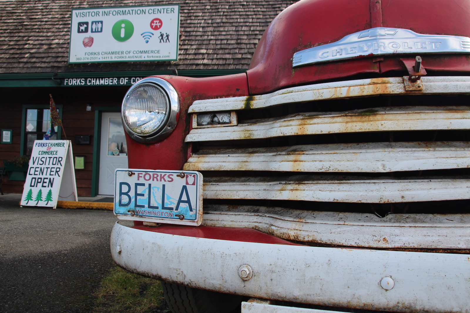 An old red truck with a dirty white grate and a license plate that says BELLA is parked in front of a building with a sign marked visitor's center