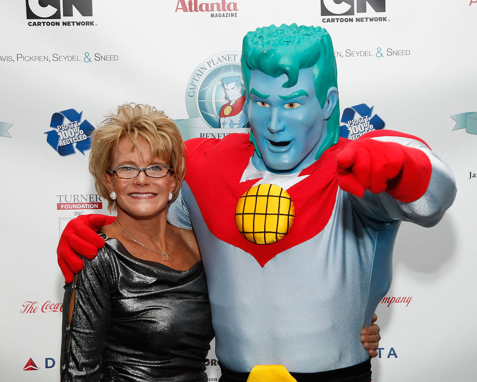 a woman in a sparkly dress on the left, a person in a captain planet costume with green hair, blue skin, and a red half-shirt on the right