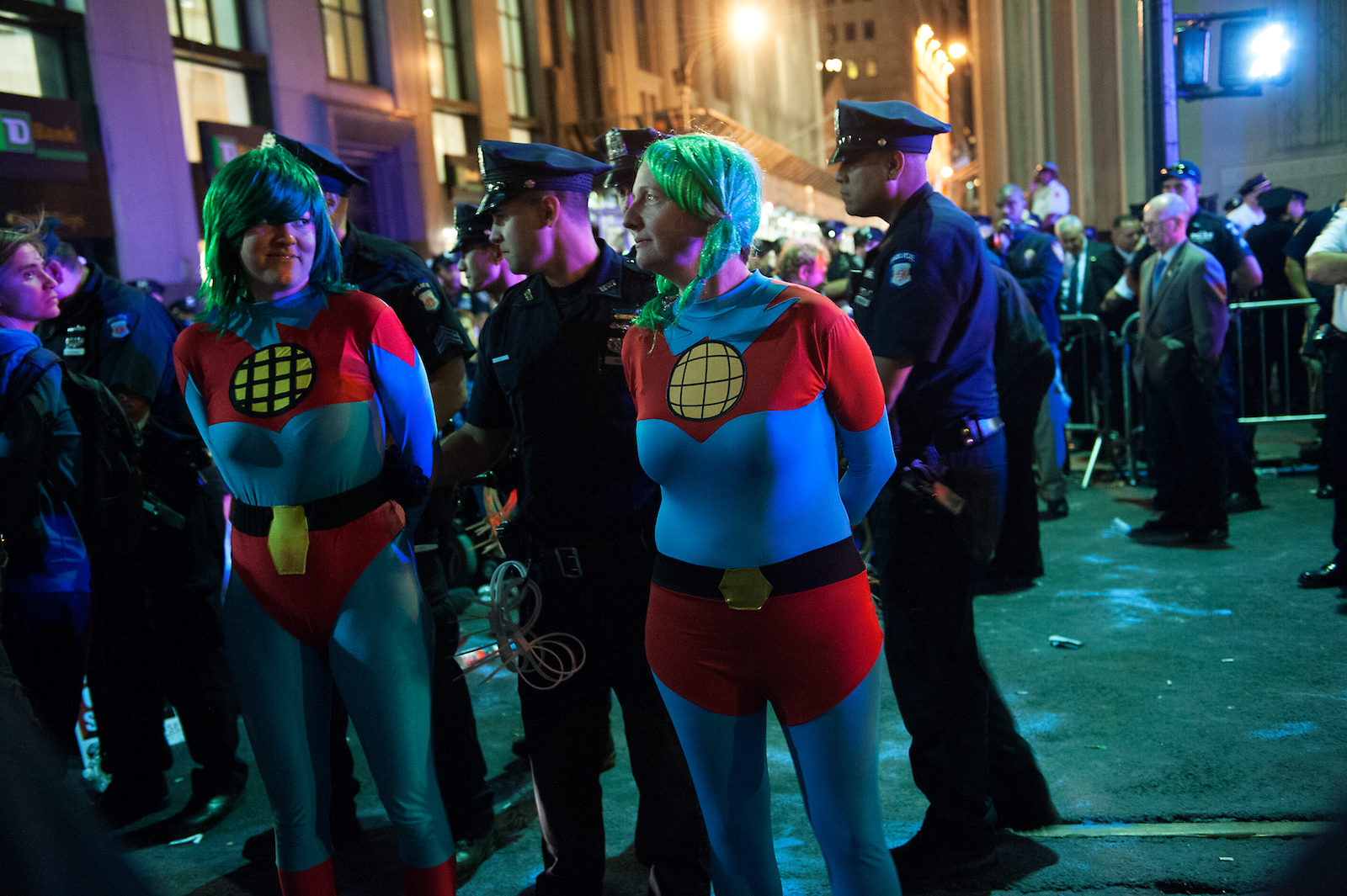 a night scene: two women in blue tights, green wigs, and red shorts are handcuffed by police on the street