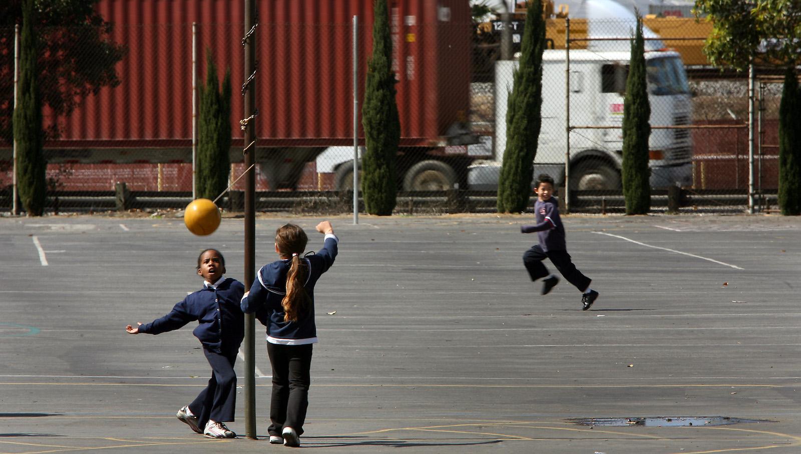 بچه ها هنگام تعطیلات در یک مدرسه ابتدایی در لس آنجلس تترابال بازی می کنند.