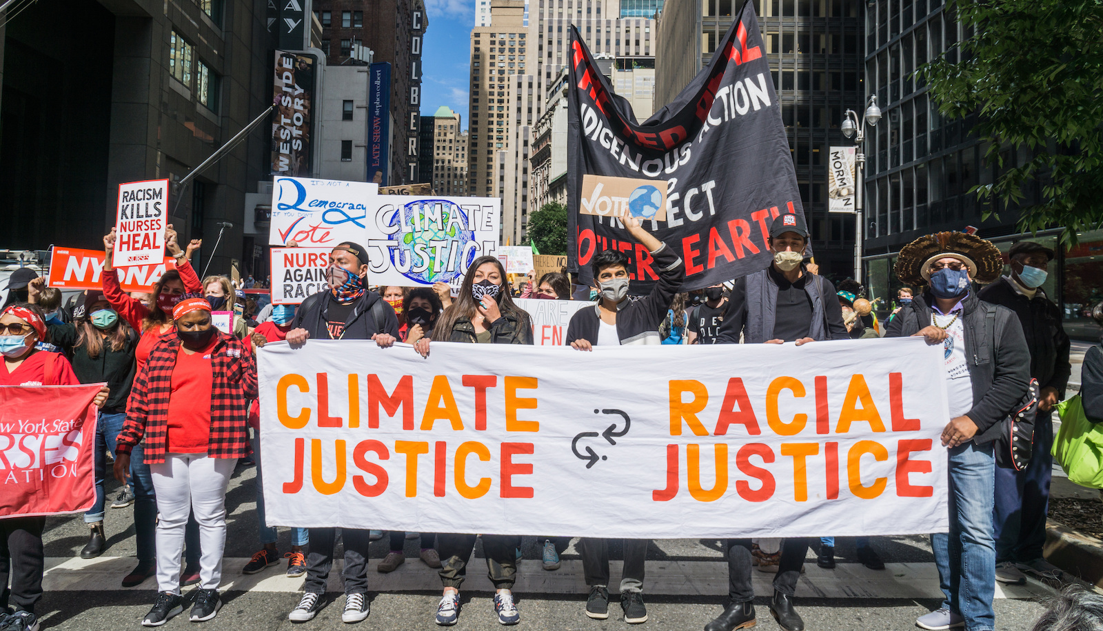protestors hold a banner that says climate justice equals racial justice