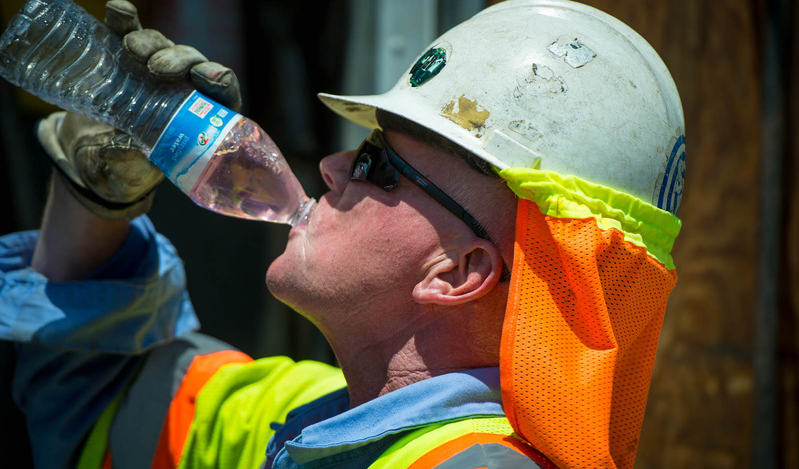 Construction worker takes a drink of water on a hot day