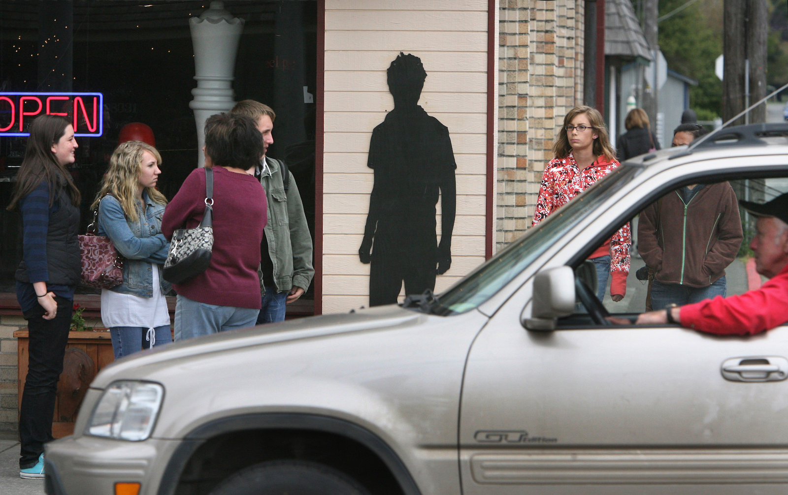 """a cut-out of """"Edward,"""" the vampire protagonist from Twilight, pasted onto the side of a building while groups of normal people stand by"""