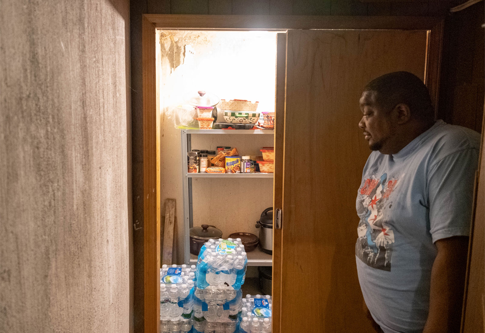A Flint, Michigan resident looks at his stockpile of bottled water
