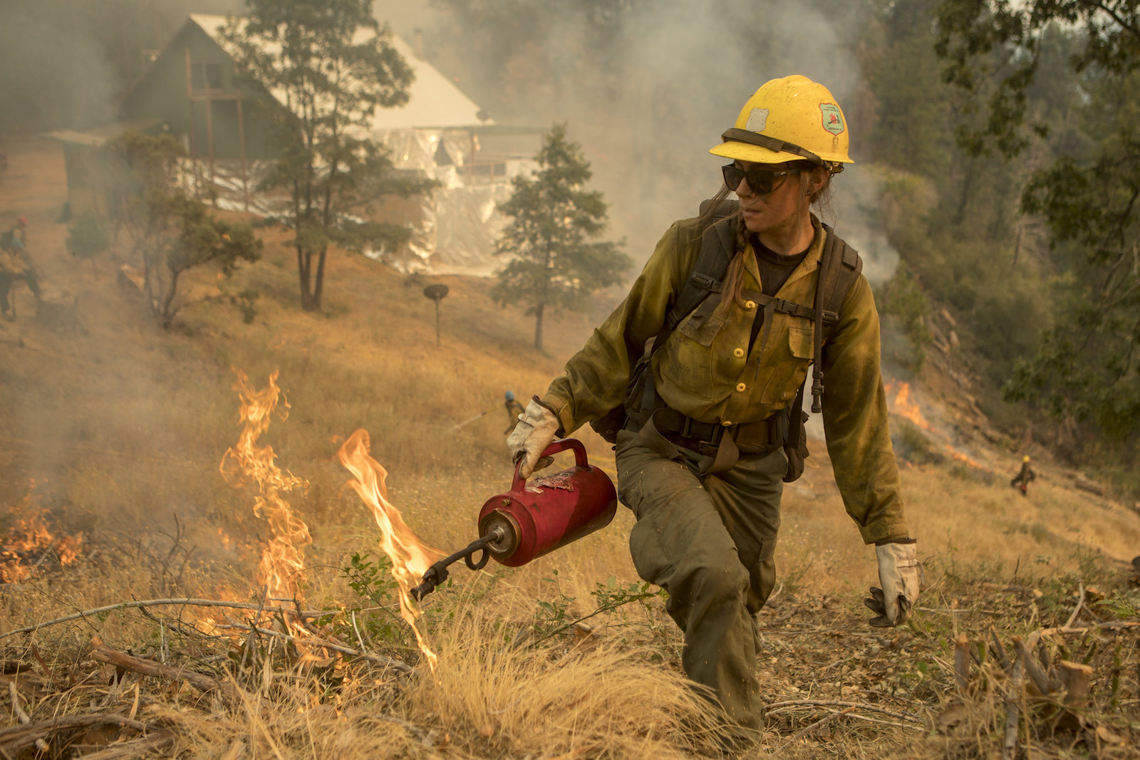 a wildland firefighter in a yellow hat and fire gear holds a red can as she walks through a dry field during a controlled burn