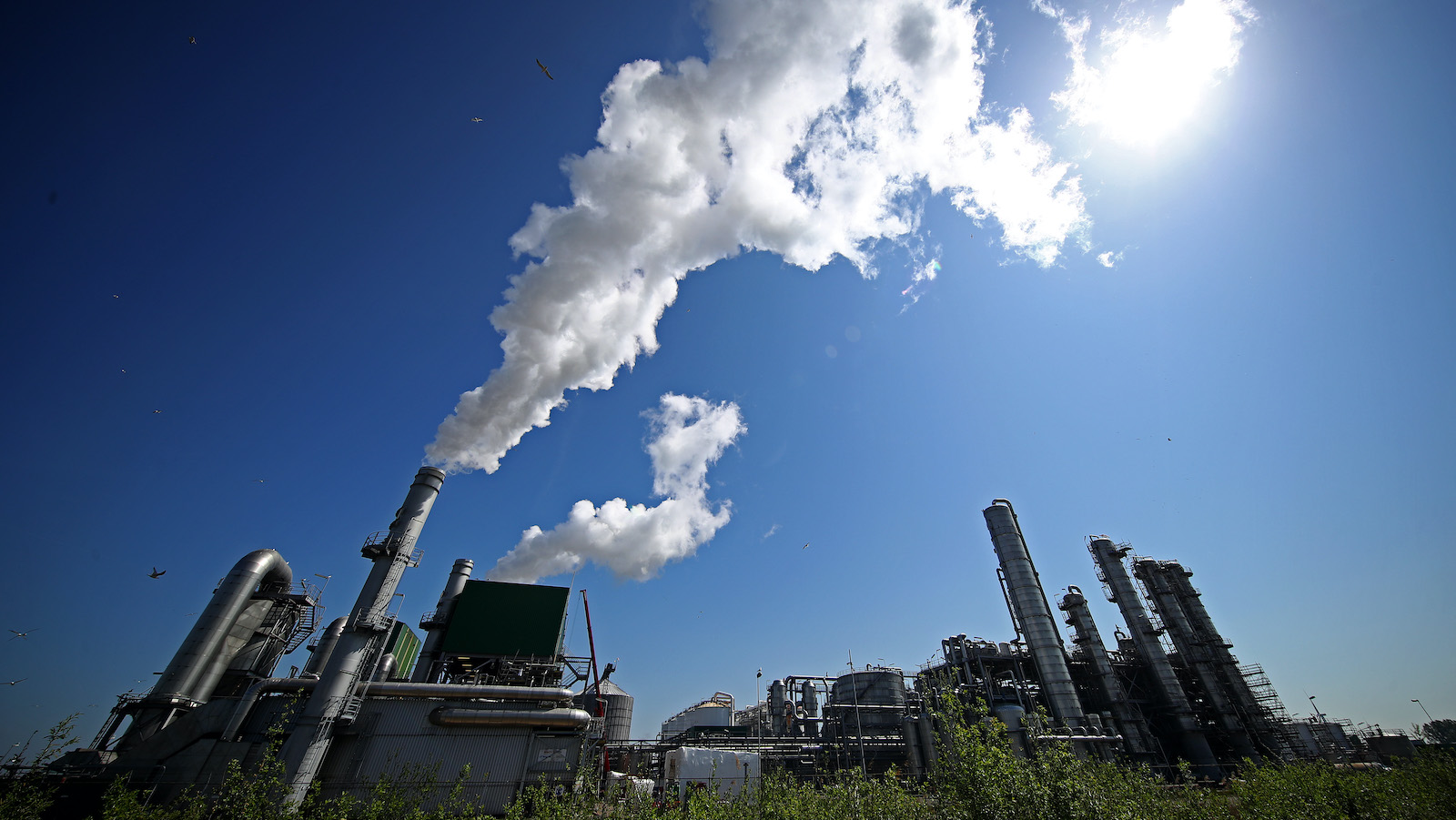 An oil refinery billows smoke.