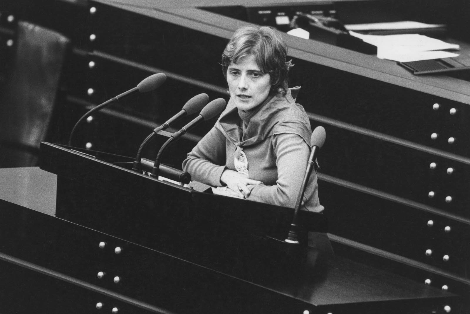 a black and white photo of a woman with short hair sitting in front of a microphone talking
