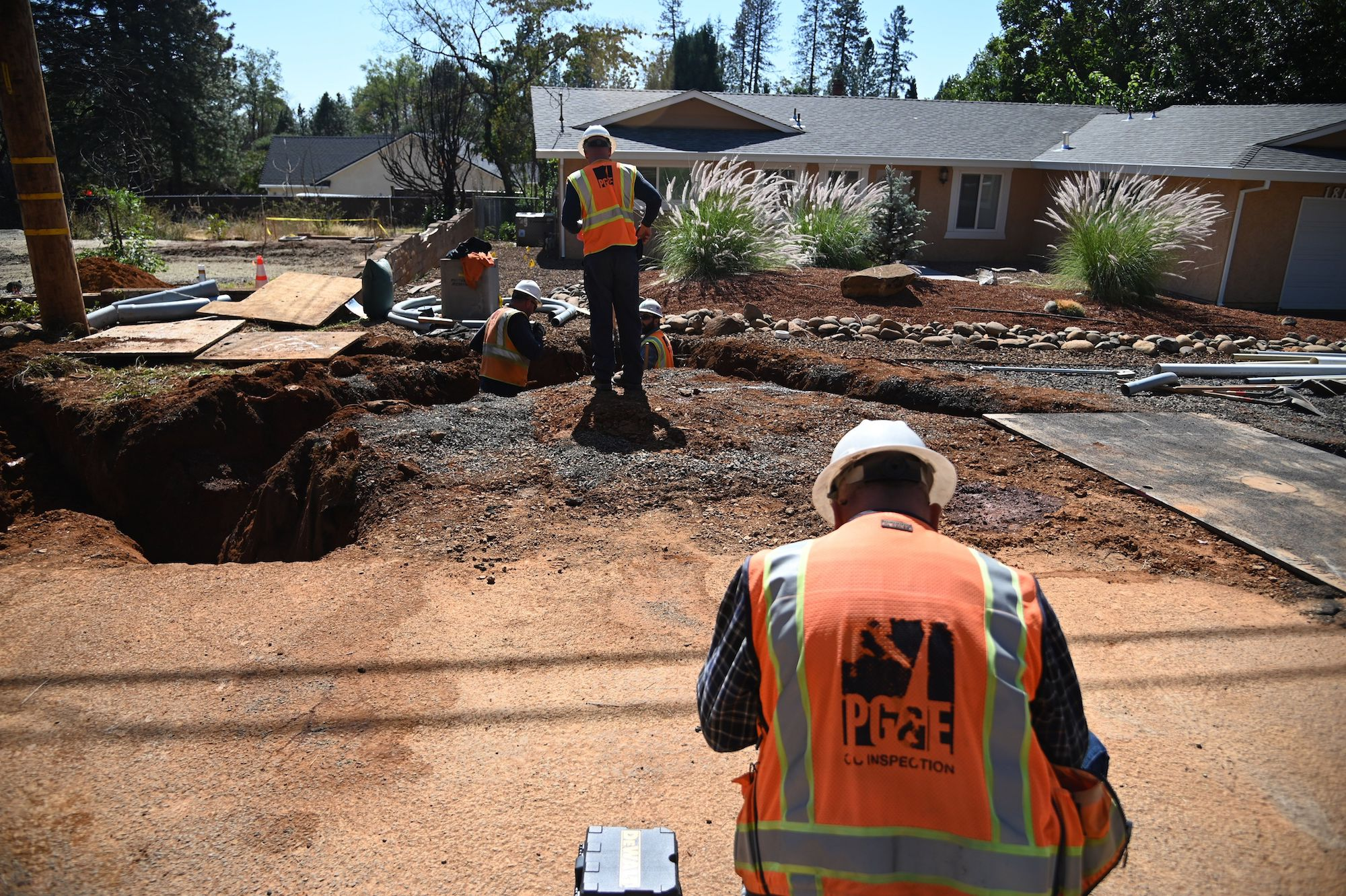 a person in an orange construction vest with PG&E on the back sits in front of a dirt path. In front of them, another worker is standing by a big hole in the dirt ground.