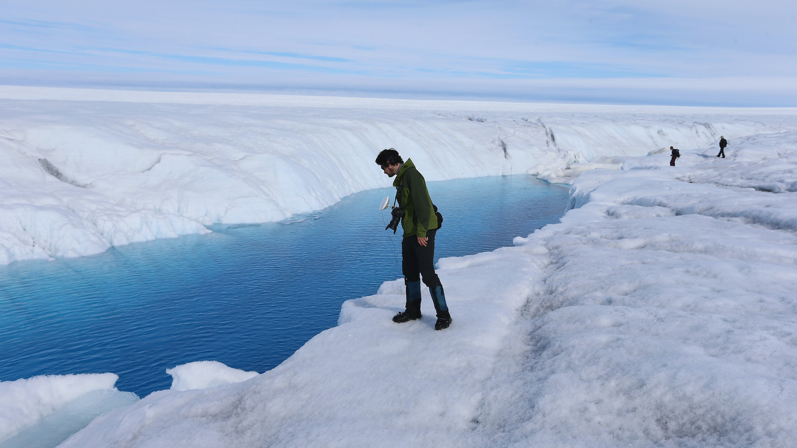 A researcher peers into the meltwater on an ice sheet.