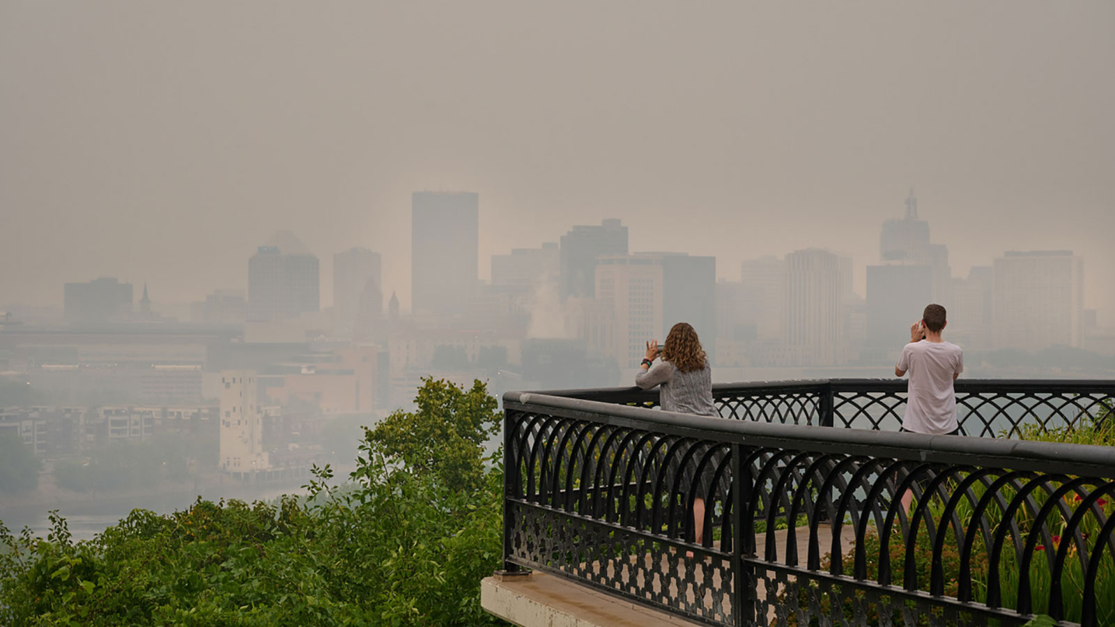 Two people in Saint Paul, Minnesota, taking photos of the city shrouded in smoke from wildfires in Canada