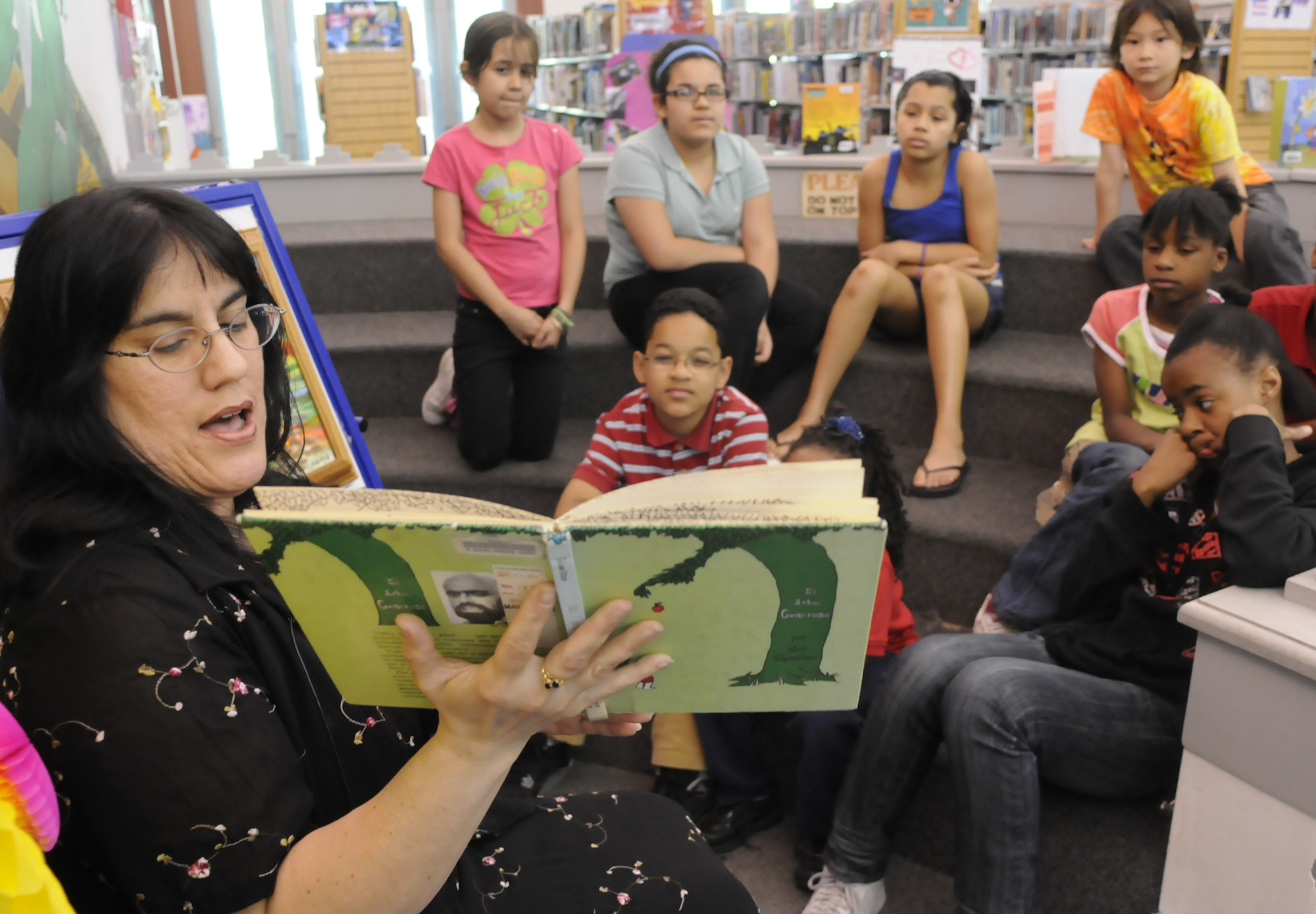 a woman with glasses holds open a copy of the giving tree with a green cover. Kids sit on risers in the background looking at the book