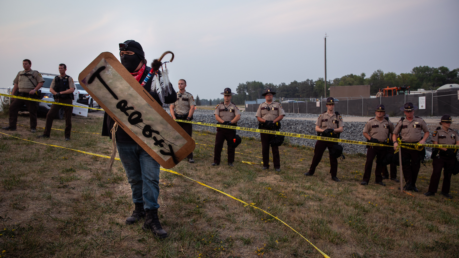 """A protestor holds a sign reading """"Treaty"""" at a drill site on the Red Lake River."""