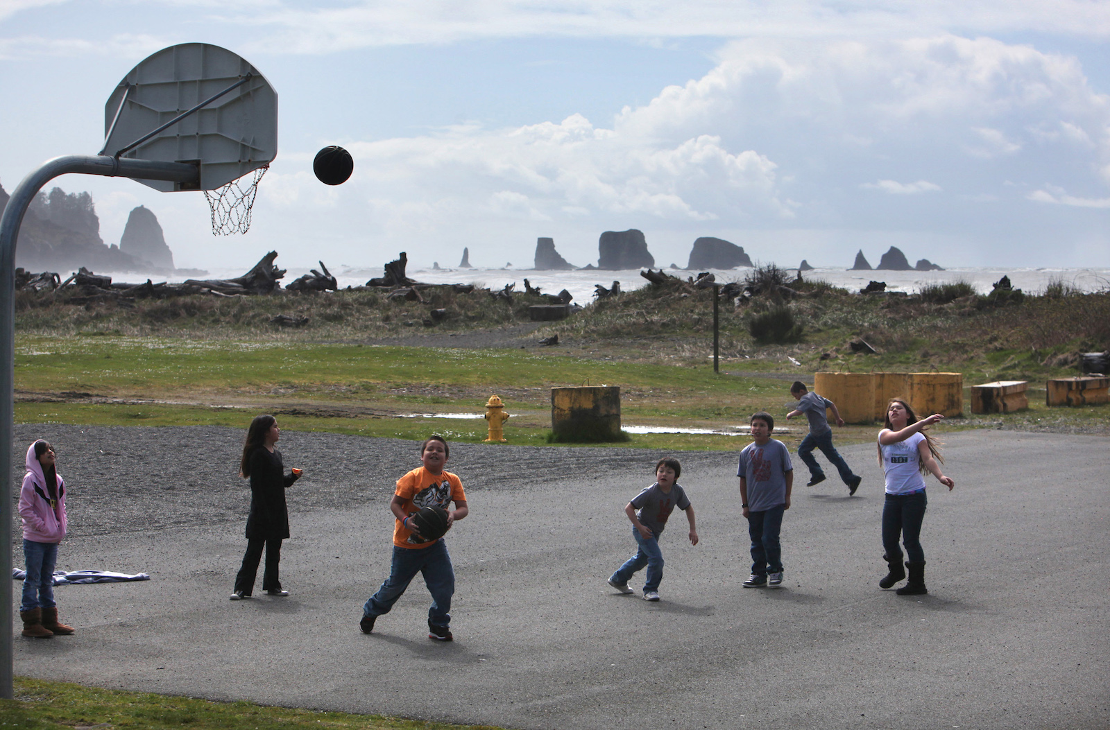 a group of kids play on a basketball court located near a rocky beach