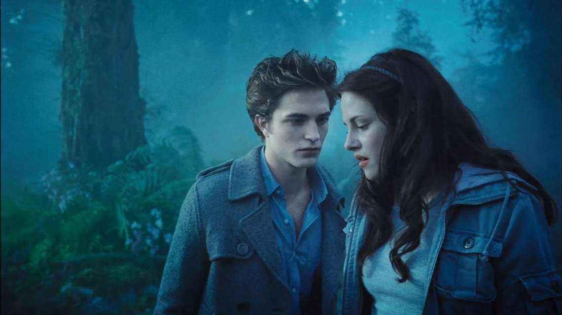 a photo still from the movie Twilight with a foggy blue tree background and Edward and Bella in the foreground