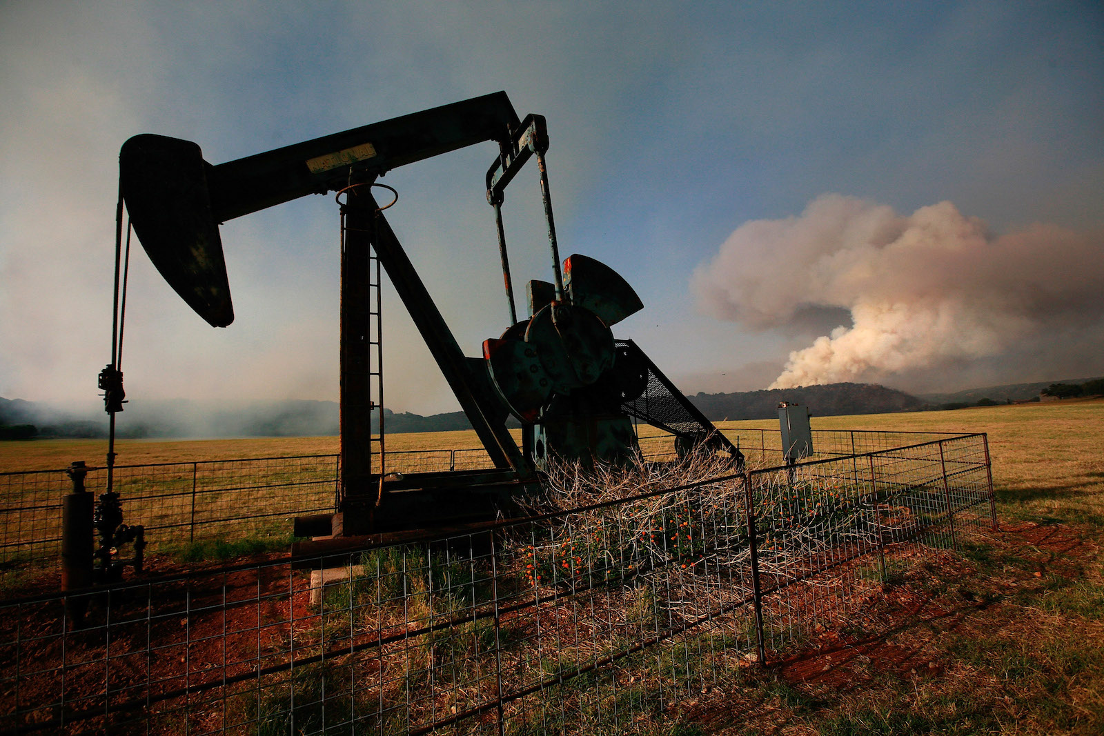 an oilfield pumpjack is silhouetted against a dry landscape. In the distance, a large white plume of smoke billows into a blue sky