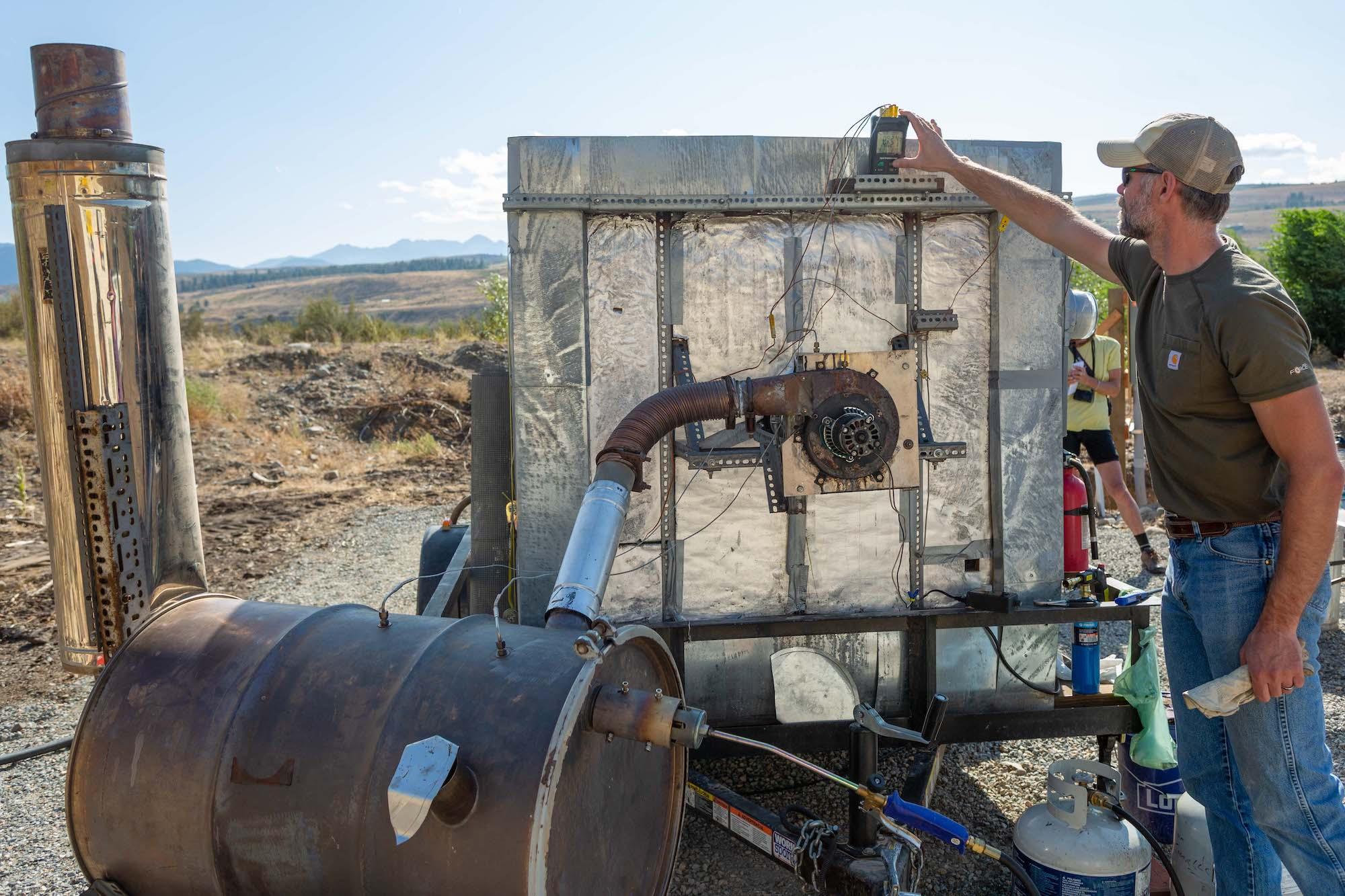 Un homme vêtu d'une chemise grise et d'un jean bleu tient un instrument de mesure sur sa main gauche pour vérifier une jauge sur une machine appelée pyrolyseur, qui ressemble à une grosse poubelle en métal reliée à un baril de métal rouillé. Il est dehors et le ciel est bleu.