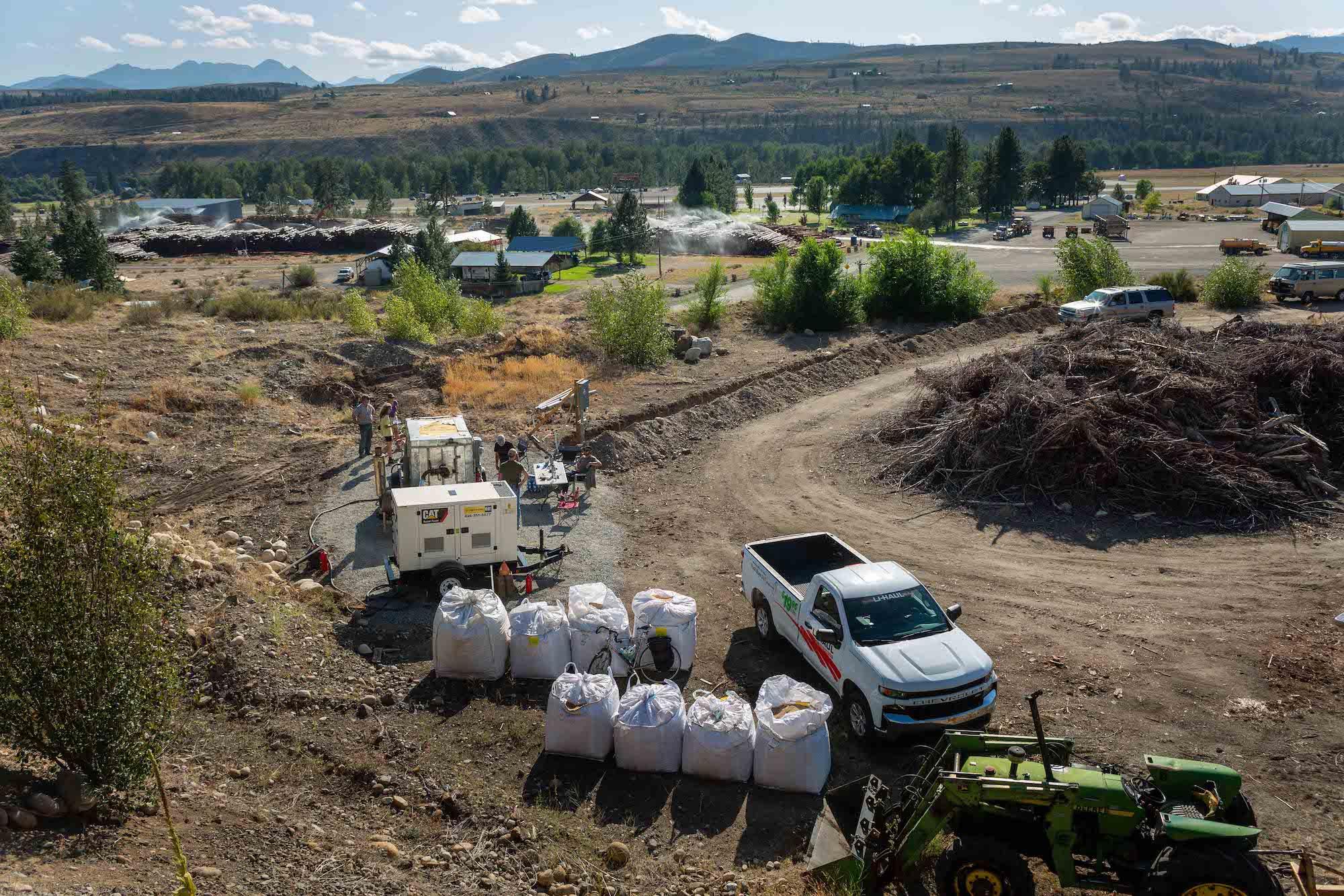 Une camionnette blanche est garée à côté de gros sacs blancs sur le bord d'une route non goudronnée.