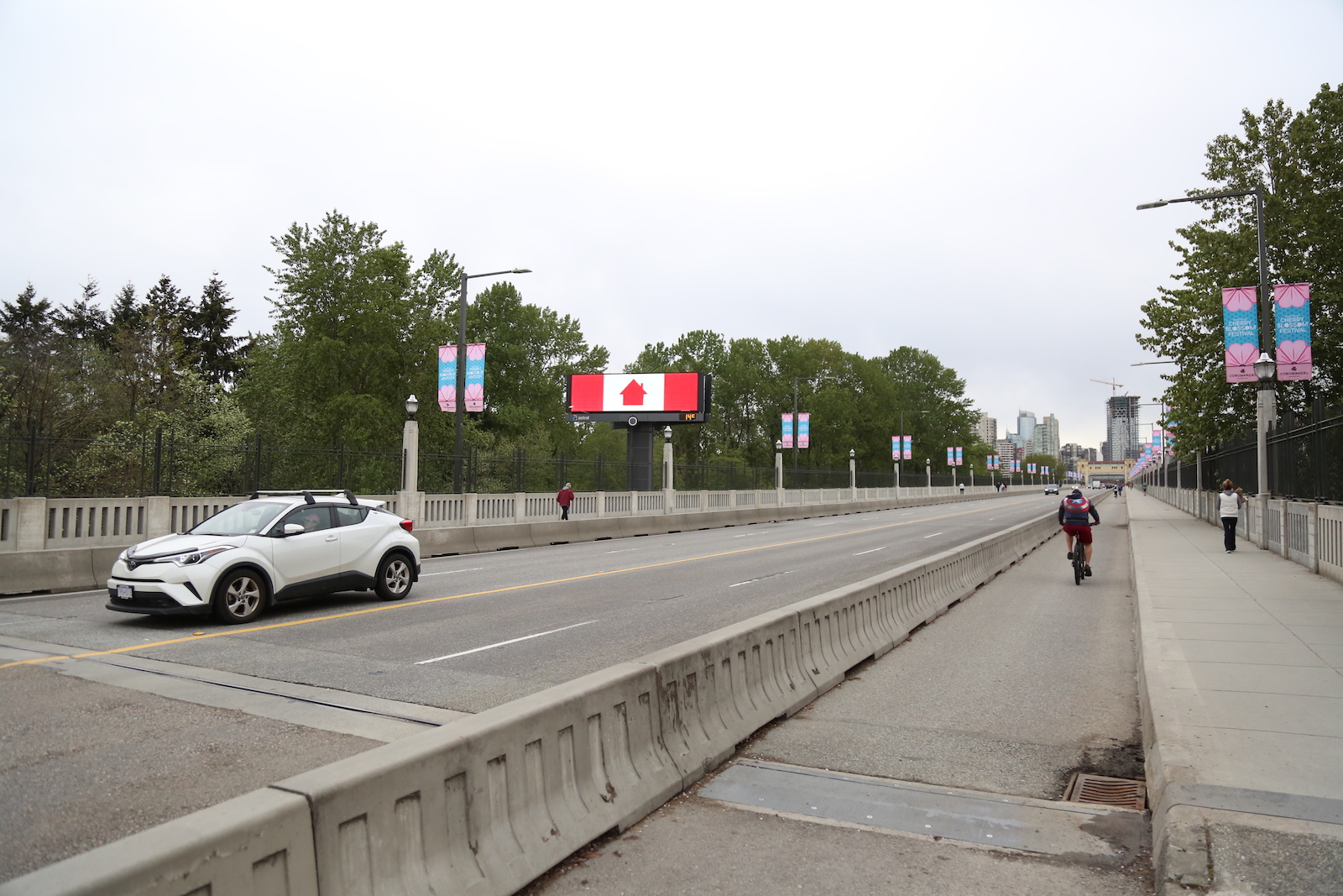 a single white car zooms on the other side of a protected bike lane with one rider. A billboard with an adaptation of the Canadian flag glows on the side of the road