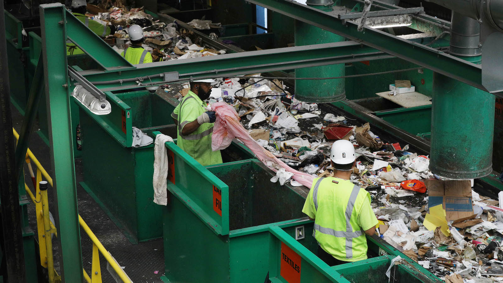 Workers sort plastic at a recycling center.
