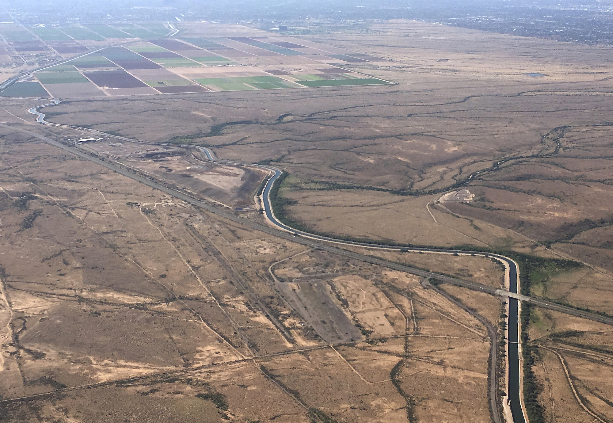an aerial view of a winding canal through brown, dry hills