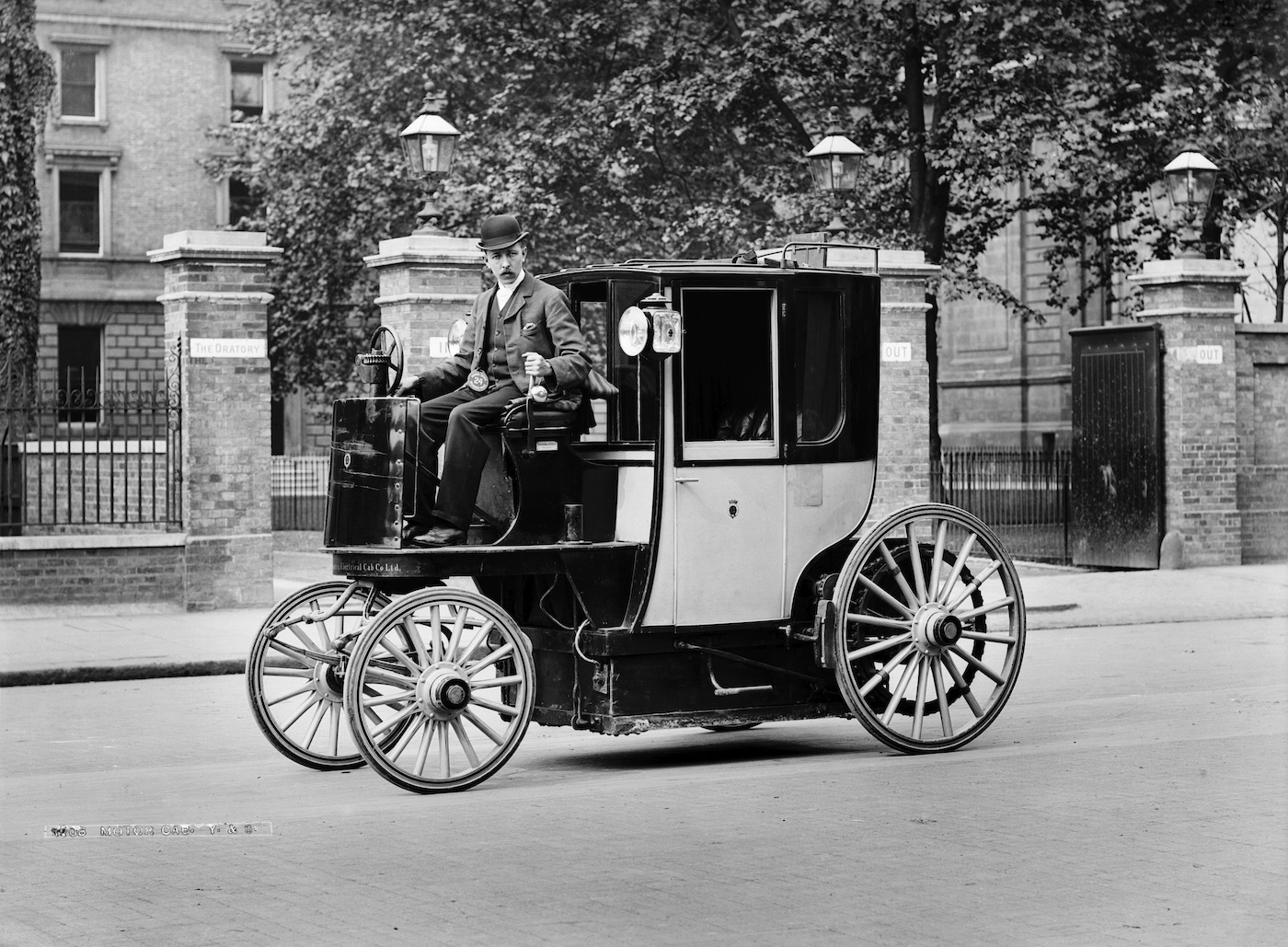 Black and white photo of an old cab on the street.