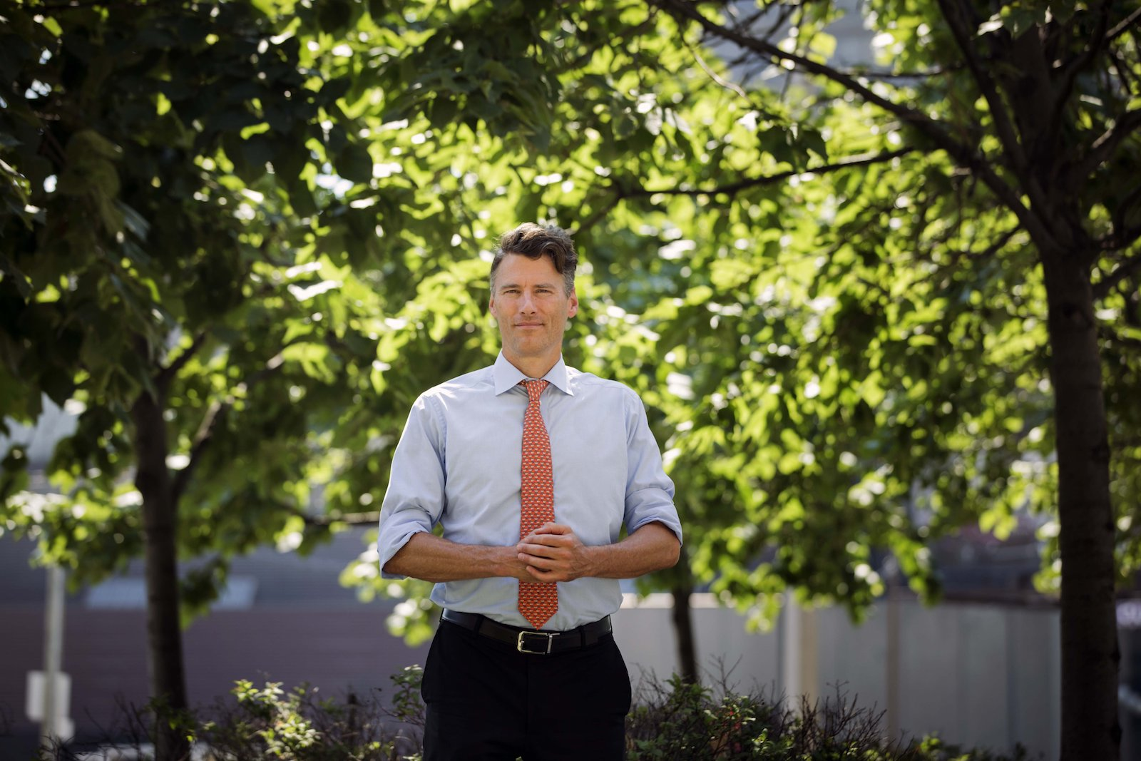 a man in a button-up shirt and a coral tie stands in a tree-filled area