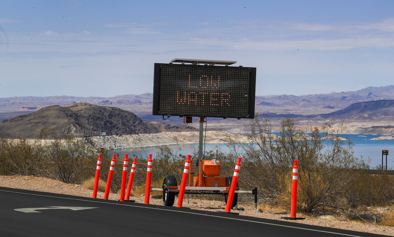 a large light-up sign near the side of a highway says low levels. The sign is surrounded by orange cones and water is visible in the background