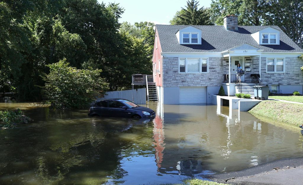 A car sits on a flooded driveway of a house following a night of heavy wind and rain from Hurricane Ida