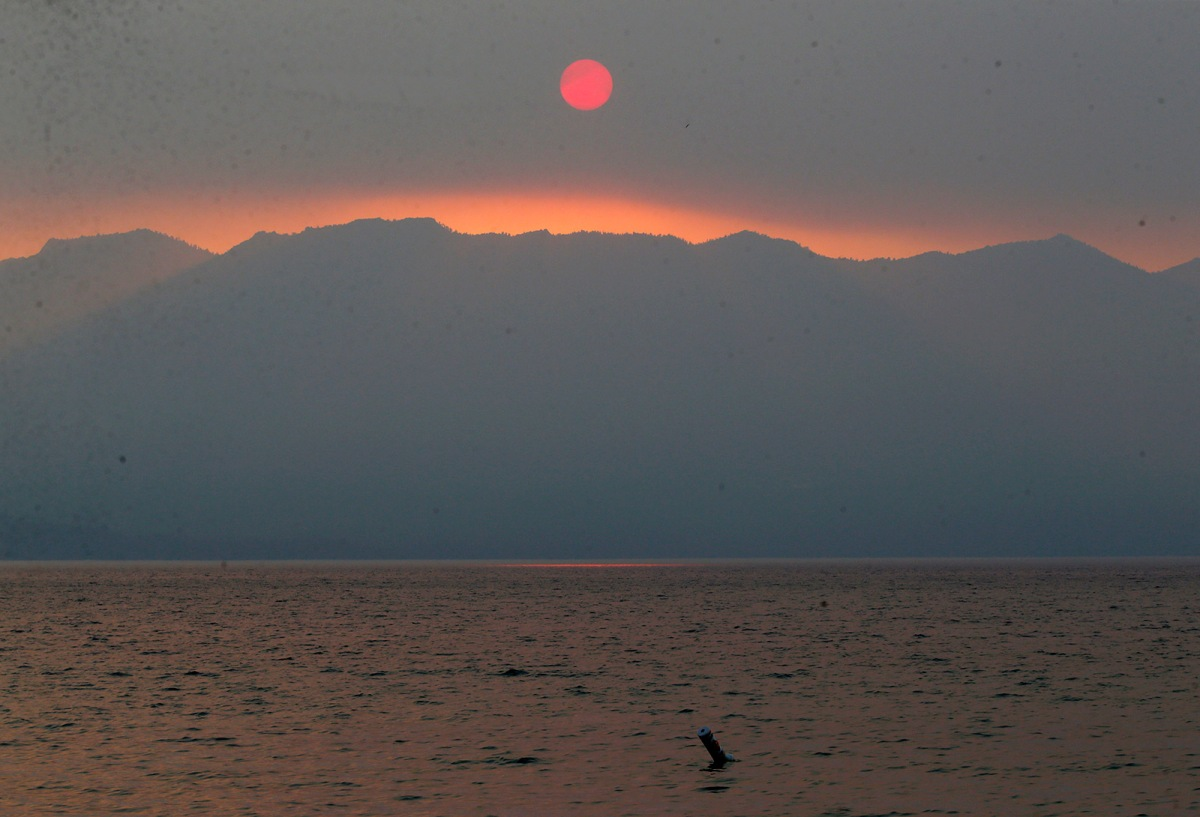 A smoky sunset is seen over Lake Tahoe in this view from Lakeside Beach in South Lake Tahoe
