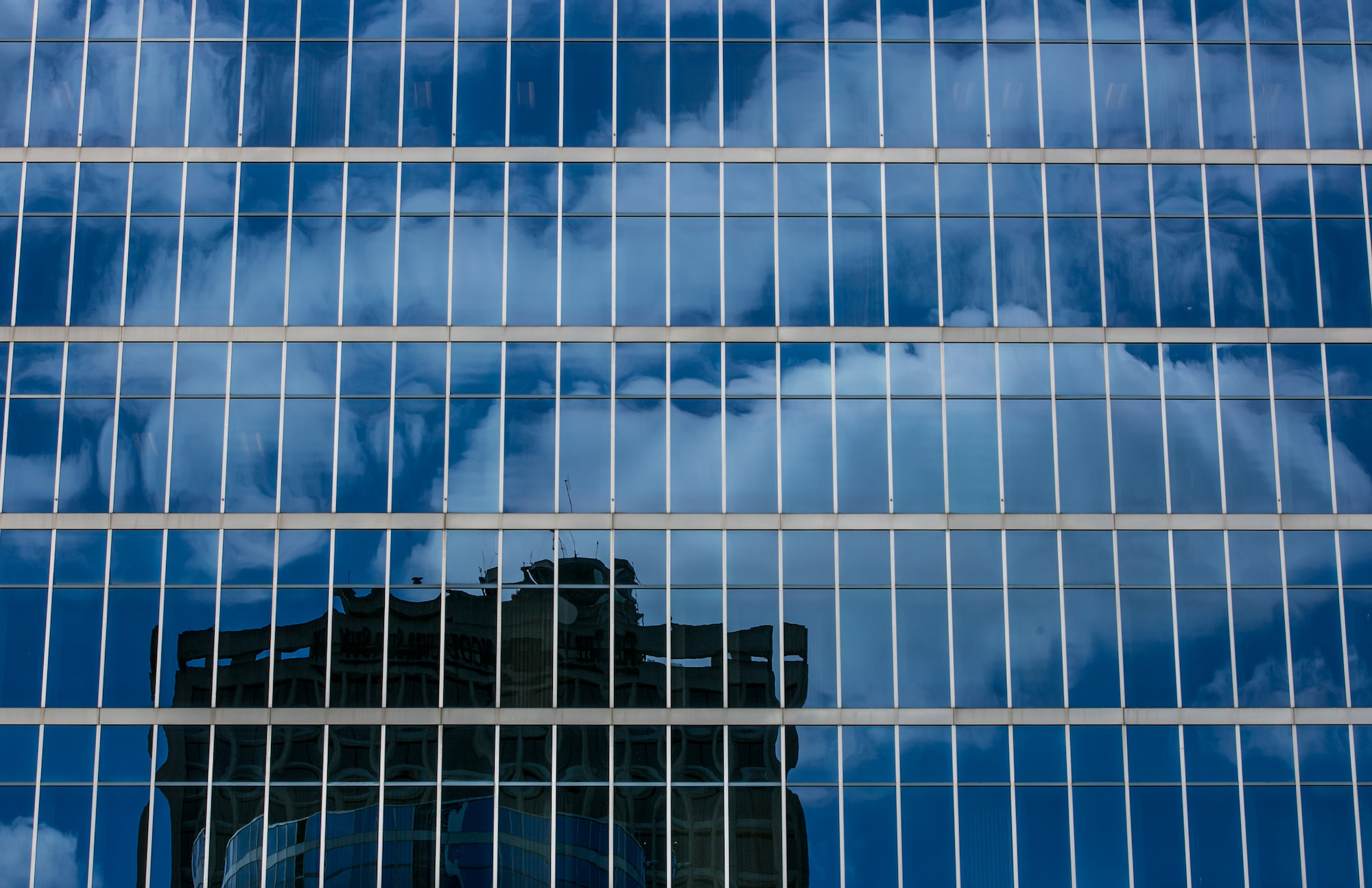 a blue glass building facade reflecting clouds, sky, and a nearby building