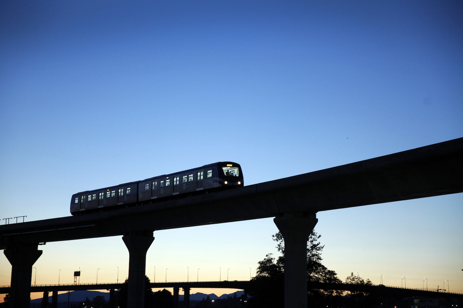 A lightrail train on an elevated road silhouetted against a darkened sky