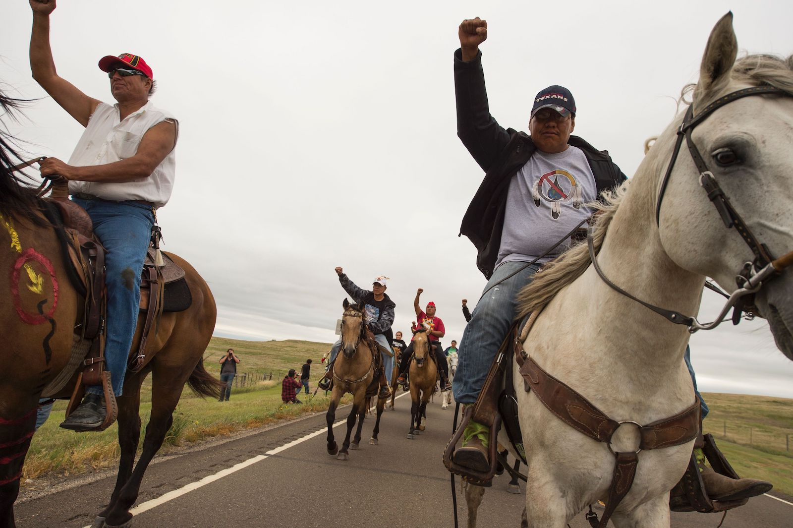Indigenous activists on horseback raise their fists in protest