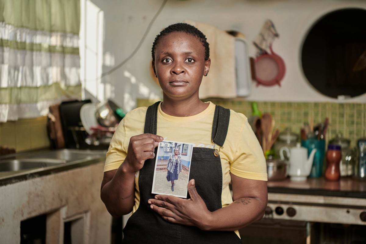 Awoman wearing a light yellow t-shirt and navy blue overalls holds a picture of her mother, an older woman. In the background you can see a kitchen with light beige walls and lime green tiles.